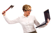 An angry business woman attacks a laptop with an axe