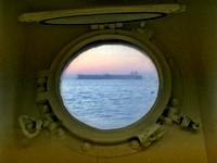 A container ship seen from a port hole