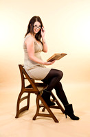 Portrait of a young attractive brunette woman with a book and library chair / steps
