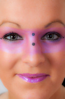 Close-up of a model with pink make-up round her eyes.