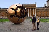 Tourists look at Sfera Conserva sculpture.
