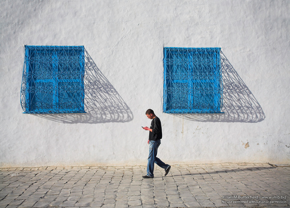 A man checks his mobile phone while walking bast traditional blue windows in Sidi Bou Said, Tunisia
