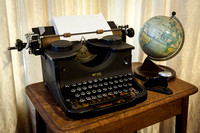 Typewriter, globe and stapler on a desk