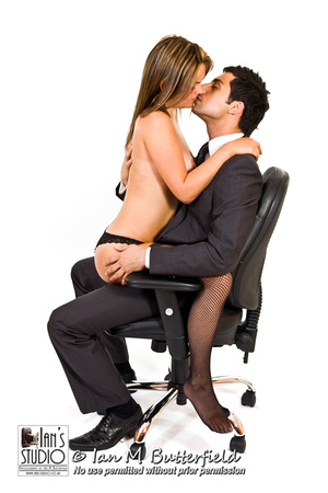 SALE 11 Apr 2014: Business man in suit sitting on office chair kissing a topless woman who is sitting on his lap