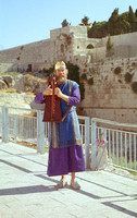 EM0713A-F00206 : A man dressed as King David playing his harp in front of temple mount, Jerusalem